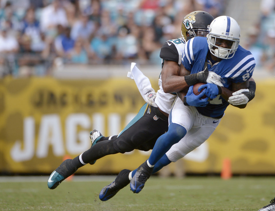 Photo - In this Sept. 29, 2013, photo, Indianapolis Colts wide receiver Reggie Wayne (87) catches a pass in front of Jacksonville Jaguars free safety Josh Evans during an NFL football game in Jacksonville, Fla.  Wayne is trying to return from a torn anterior cruciate ligament in his right knee. (AP Photo/Phelan M. Ebenhack)