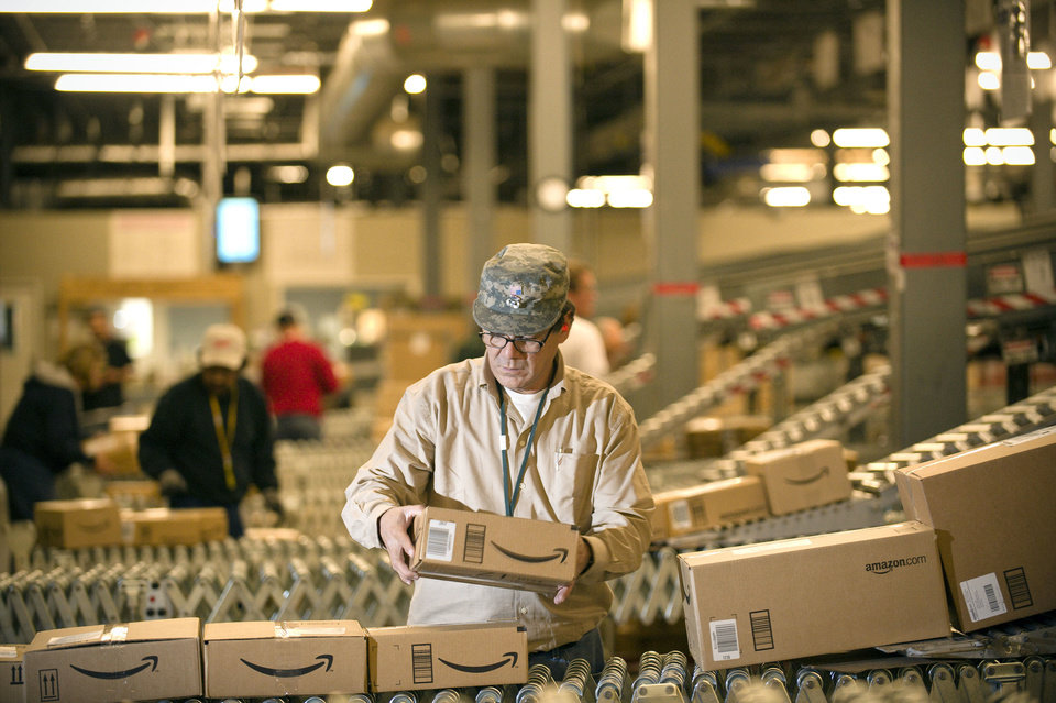An Amazon.com employee grabs boxes off the conveyor belt to load in a truck at their Fernley, Nev., warehouse. Amazon.com Inc. says it is adding 5,000 full-time and 2,000 part-time jobs in 13 states, beefing up staff at the warehouses where it fills orders, and in its customer service division. AP Photo Scott Sady