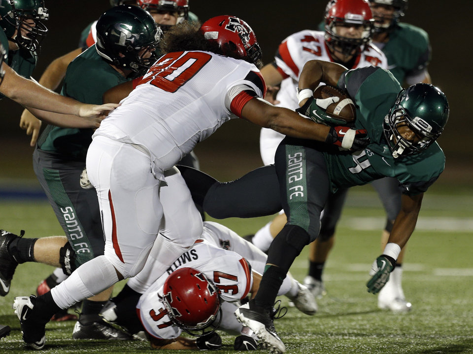 Edmond Santa Fe's Ke'Marrie Carter-Hartfield dives forwards as Mustangs' Xavier Whitehead (90) and Cutter Smith tackle him during the high school football game between Edmond Santa Fe and Mustang at Wantland Stadium in Edmond, Okla.,   Thursday, Oct. 3, 2013. Photo by Sarah Phipps, The Oklahoman