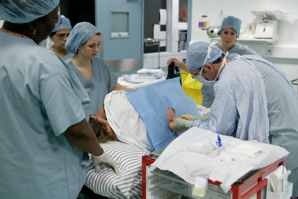 AN90T3 A woman receiving an injection into the spine in theatre before assisted birth