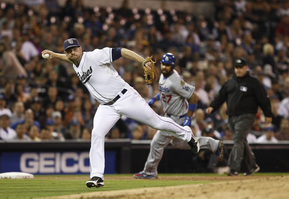 Photo -   San Diego Padres third baseman Chase Headley prepares tp fire a throw after fielding a slow roller hit by Los Angeles Dodgers' Hanley Ramirez as the Dodgers' Matt Kemp rounds third during sixth inning of a baseball game Tuesday, Sept. 25, 2012 in San Diego. (AP Photo/Lenny Ignelzi)