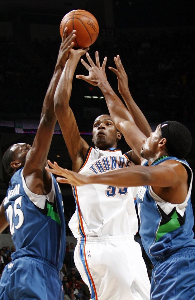 Photo - Oklahoma City's Kevin Durant shoots between Minnesota's Al Jefferson, left, and Ryan Gomes during the NBA basketball game between the Oklahoma City Thunder and the Minnesota Timberwolves at the Ford Center in Oklahoma City, Friday, Nov. 28, 2008. Minnesota won, 105-103. BY NATE BILLINGS, THE OKLAHOMAN