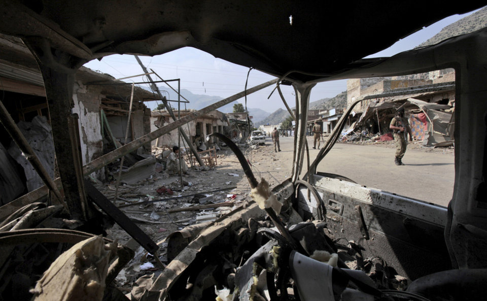 Photo -   Seen through the wreckage of a vehicle, Pakistani Army soldiers check the site of a car bomb explosion in the Pakistani town of Darra Adam Khel in the troubled Khyber Pakhtunkhwa province bordering Afghanistan, Saturday, Oct. 13, 2012. A powerful car bomb went off outside the offices of pro-government tribal elders in northwestern Pakistan on Saturday, killing several people, police said. (AP Photo/Mohammad Sajjad)