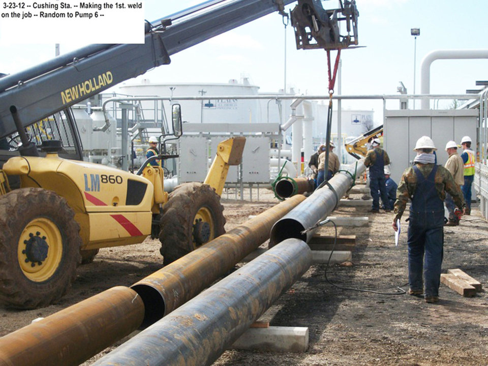 Photo - Workers prepare to make the first weld at the origination point of the Seaway pipeline in Cushing.