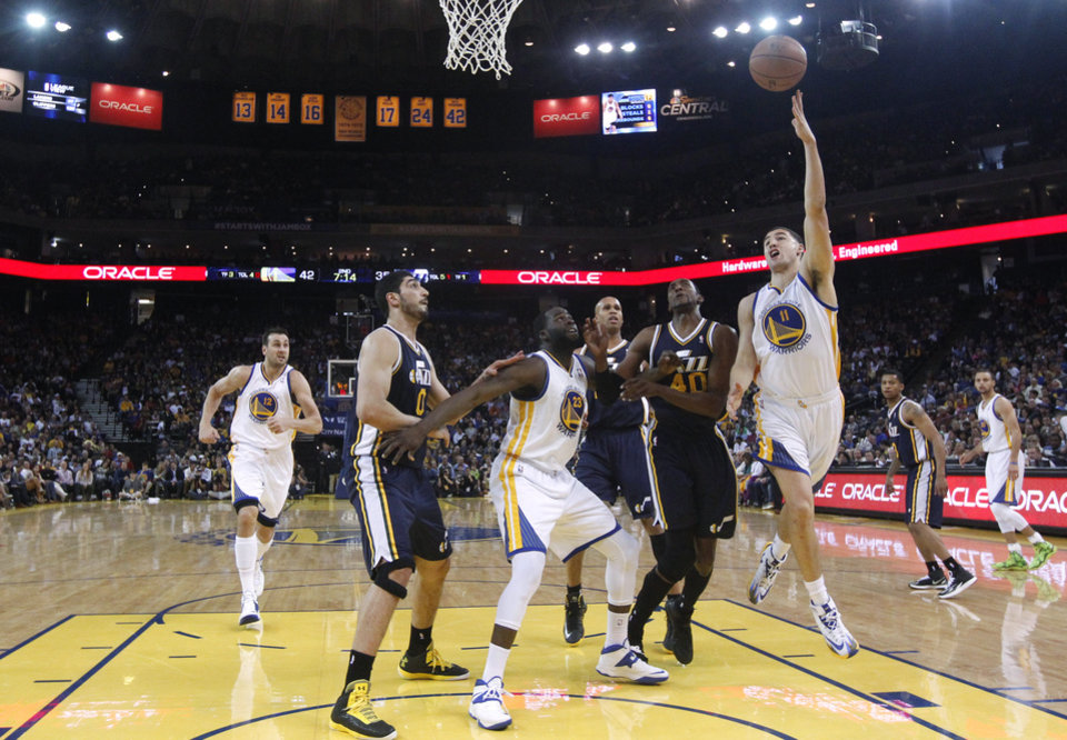 Photo - Golden State Warriors guard Klay Thompson, right, goes up for a shot against the Utah Jazz during the first half of an NBA basketball game Sunday, April 6, 2014, in Oakland, Calif. (AP Photo/Marcio Jose Sanchez)