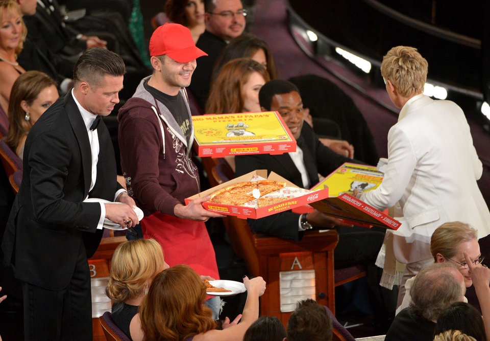 Photo - Brad Pitt, left, and Ellen DeGeneres, right, pass out pizza in the audience during the Oscars at the Dolby Theatre on Sunday, March 2, 2014, in Los Angeles.  (Photo by John Shearer/Invision/AP)