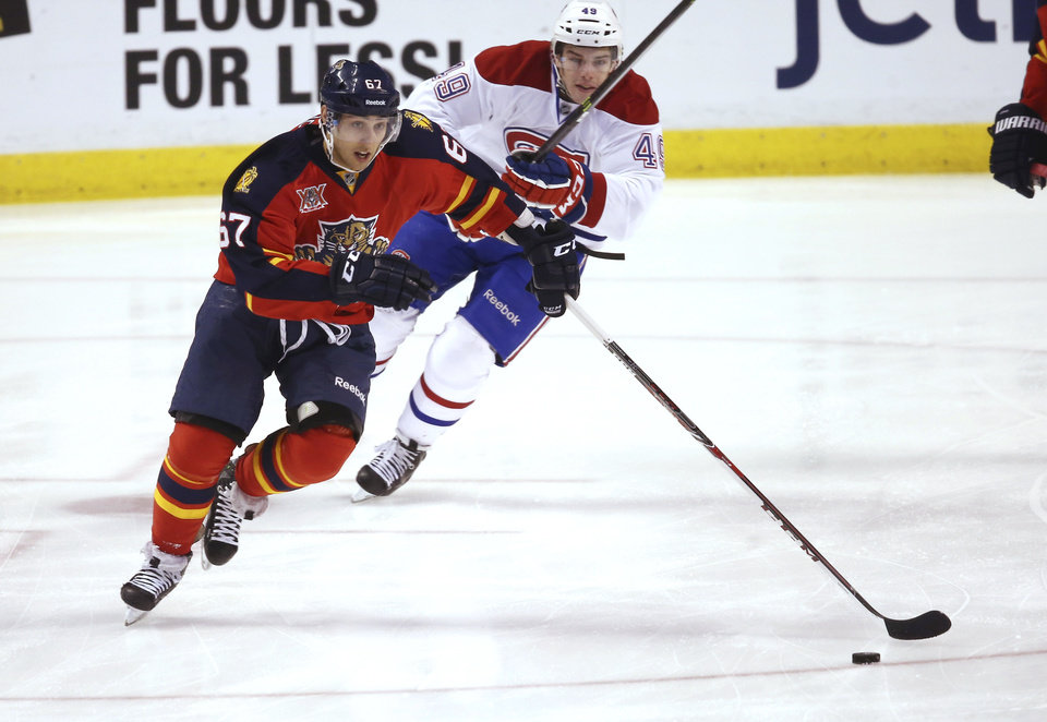 Photo - Montreal Canadiens' Michael Bournival (49 chases Florida Panthers' Vincent Trocheck (67) trying to steal the puck during the first period of an NHL hockey game in Sunrise, Fla., Saturday, March 29, 2014. (AP Photo/J Pat Carter)