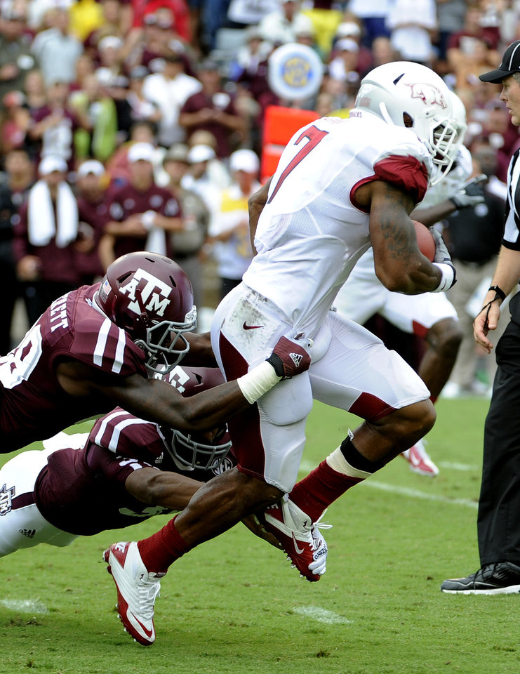 Photo -   Arkansas running back Knile Davis (7) drags Texas A&M defenders Deshazor Everett (29) and Howard Matthews, center, during the first half of an NCAA college football game Saturday, Sept. 29, 2012, in College Station, Texas. (AP Photo/Pat Sullivan)