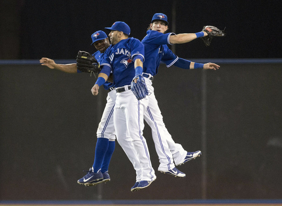 Photo - Toronto Blue Jays' Rajai Davis, left,  Jose Bautista, center,  and Colby Rasmus celebrate their 4-2 win over the Baltimore Orioles after a  baseball game in Toronto, Saturday June 22, 2013. (AP Photo/the Canadian Press, Chris Young)