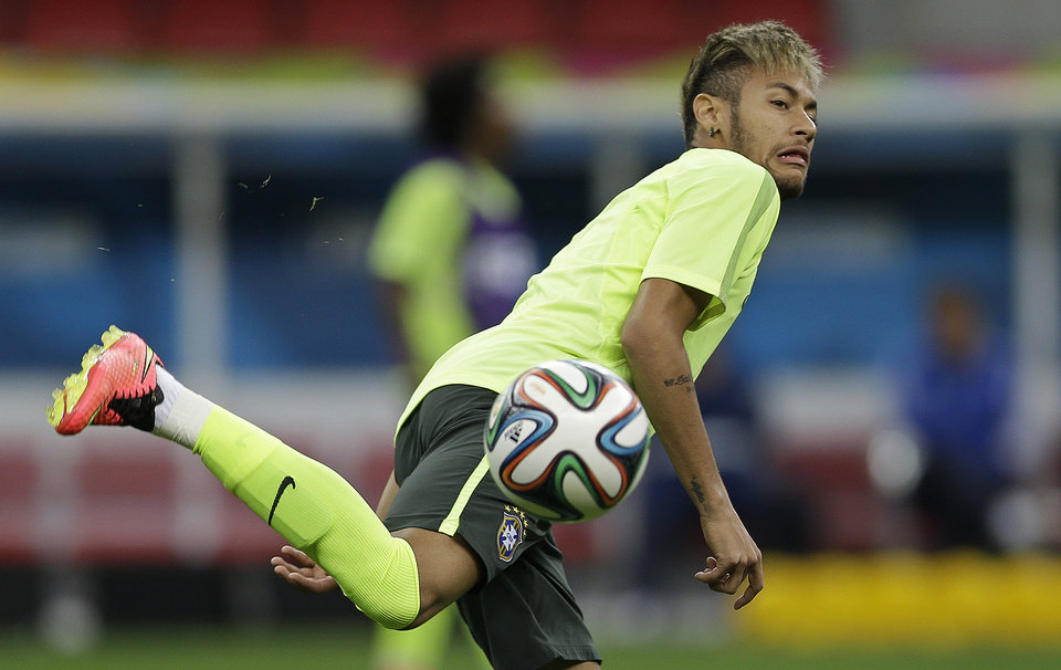 Photo - Brazil's Neymar practices during an official training session the day before the group A World Cup soccer match between Brazil and Cameroon at the Estadio Nacional in Sunday, June 22, 2014. The hosts need at least a draw to advance to the second round, and a win will likely secure first place. Cameroon is already eliminated after losing its first two matches. (AP Photo/Andre Penner)