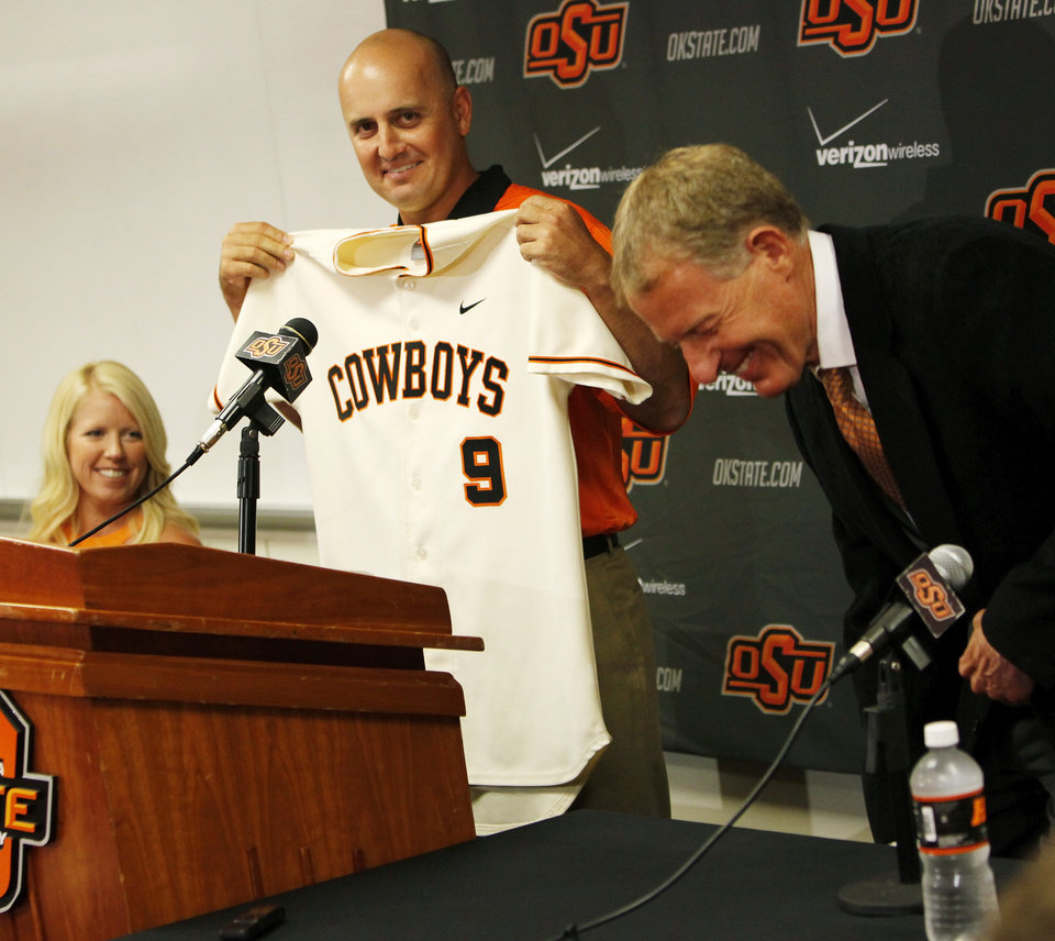 Josh Holliday holds up a jersey presented to him by OSU athletics director Mike Holder, right, as Josh Holliday's wife, Jenny Holliday, looks on during a press conference at Oklahoma State University to introduce Josh Holliday as OSU's new head baseball coach, in Stillwater, Okla., Friday, June 8, 2012. Photo by Nate Billings, The Oklahoman