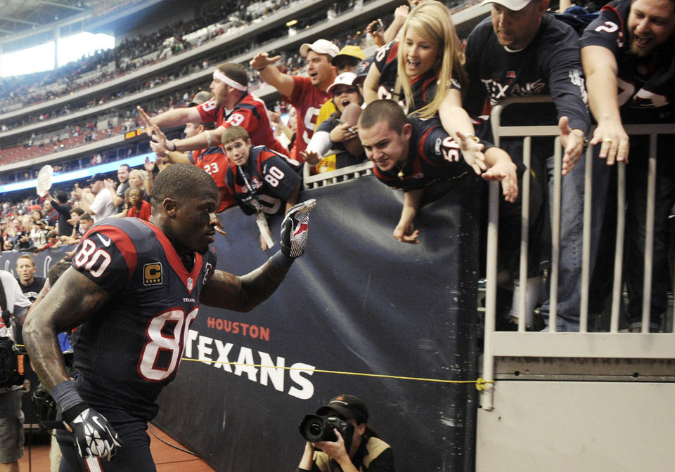 Photo -   Houston Texans' Andre Johnson (80) slaps hands with fans as he runs off the field after an NFL football game against the Jacksonville Jaguars, Sunday, Nov. 18, 2012, in Houston. Johnson scored the winning touchdown in overtime to defeat the Jaguars 43-37. (AP Photo/Dave Einsel)