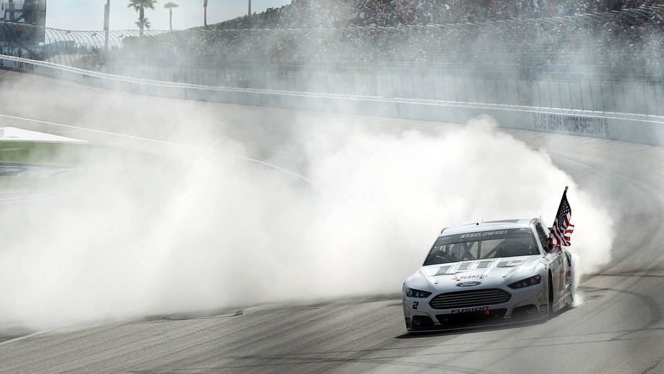 Photo - Brad Keselowski does a burnout after winning a NASCAR Sprint Cup Series auto race Sunday, March 9, 2014, in Las Vegas. (AP Photo/Isaac Brekken)