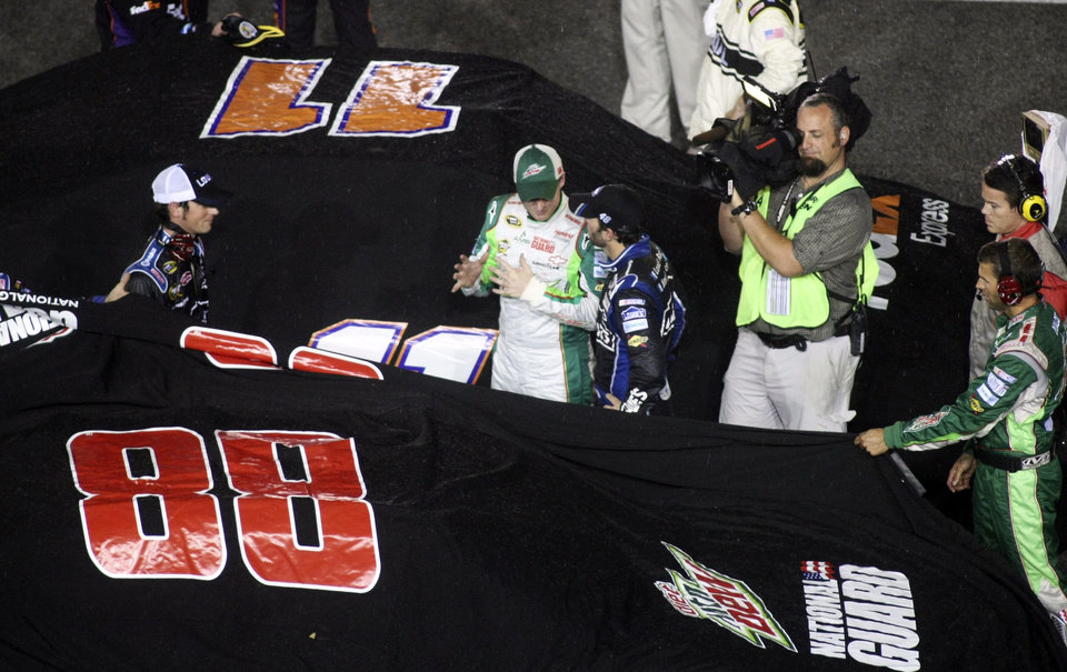 Photo -   Dale Earnhardt Jr., center left, talks with Jimmie Johnson, center right, during a rain delay at the NASCAR Sprint Cup Series auto race at Richmond International Raceway in Richmond, Va., Saturday, Sept. 8, 2012. (AP Photo/Jason Hirschfeld)