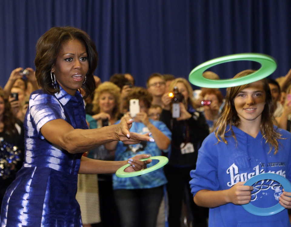 Photo - First Lady Michelle Obama partakes in an event at Watertown High School to encourage people to drink more water, Thursday, Sept. 12, 2013, in Watertown, Wis. (AP Photo/Morry Gash)