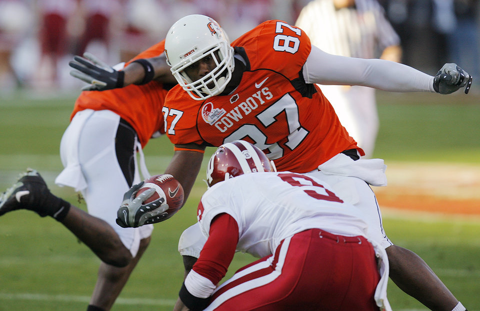 Photo - Oklahoma State's Brandon Pettigrew (87) tries to get past Indiana's Tracy Porter (9) during the Insight Bowl college football game between Oklahoma State University (OSU) and the Indiana University Hoosiers (IU) at Sun Devil Stadium on Monday, Dec. 31, 2007, in Tempe, Ariz. 