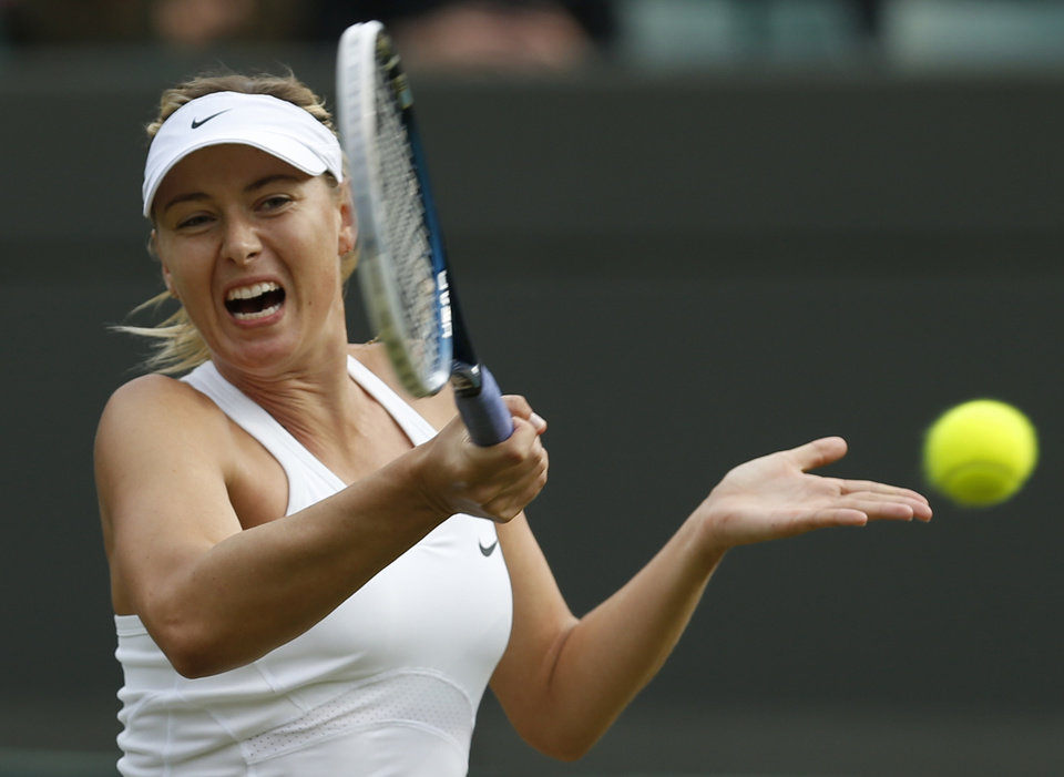 Photo - Maria Sharapova of Russia plays a return to Timea Bacsinszky of Switzerland during their women's singles match at the All England Lawn Tennis Championships in Wimbledon, London, Thursday, June 26, 2014. (AP Photo/Ben Curtis)