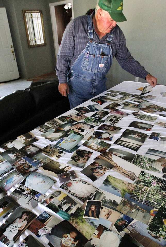 Howard Adams sorts through more than 100 photographs spread across a table in the front room of his home. The pictures were gathered from two trailer homes on the property of Rial and Mary Francis Allen after a killer tornado roared through sections of Woodward last weekend. Adams and his wife, Joyce, will clean the photos and return them to the Allens. Photo taken Tuesday, April 17, 2012. Photo by Jim Beckel, The Oklahoman