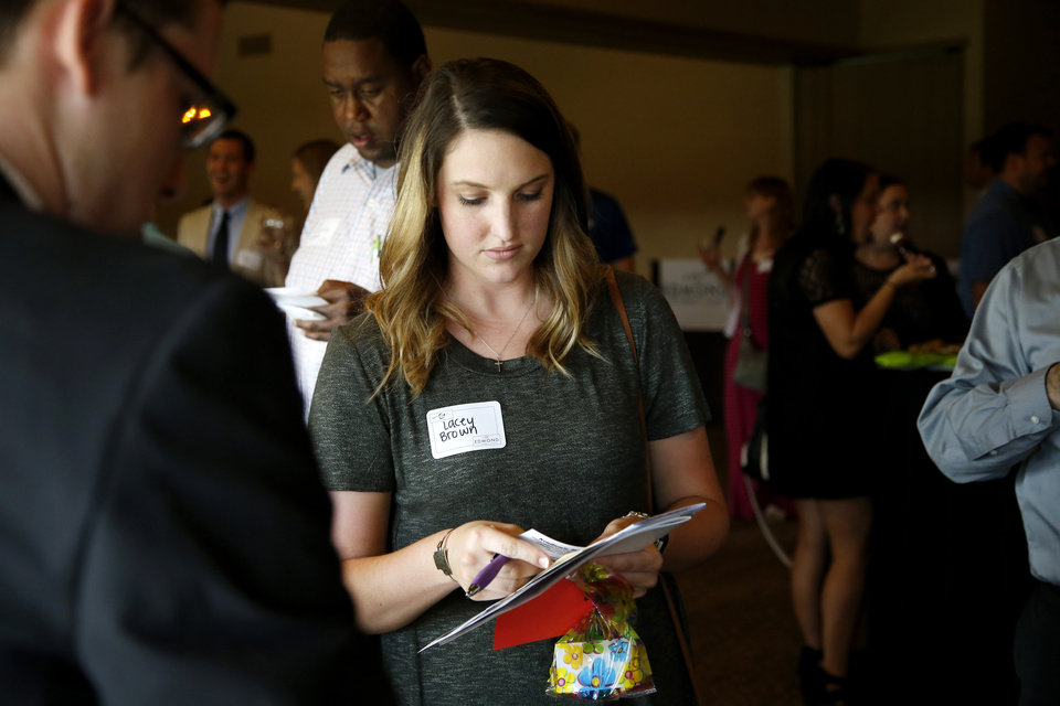 Photo -  Deer Creek High School teacher Lacey Brown gathers information during the Edmond Area Chamber of Commerce reception for new teachers. [PHOTO BY BRYAN TERRY, THE OKLAHOMAN]