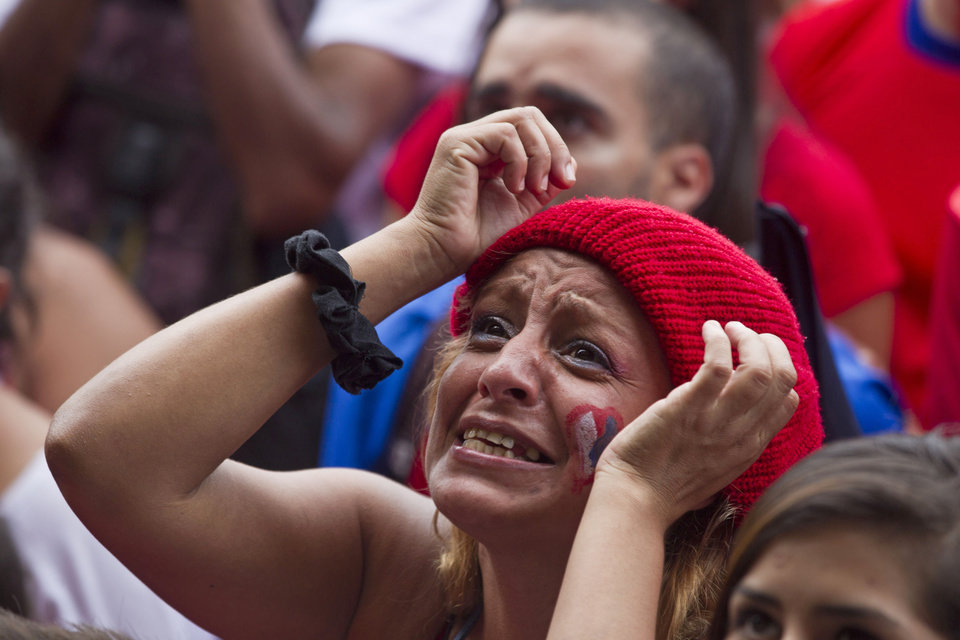 Photo - A Costa Rica soccer fan watches her team's World Cup round of 16 match against Greece on TV set up in a public square in San Jose, Costa Rica, Sunday, June 29, 2014. (AP Photo/Esteban Felix)