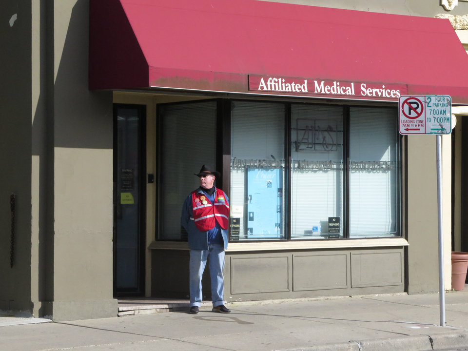 Photo - David Ritz, 65, stands as a volunteer escort outside Affiliated Medical Services, a Milwaukee abortion clinic, on Wednesday, May 28, 2014, in Milwaukee. From Texas to Alabama, laws are being enacted that would greatly restrict access to abortion, forcing many women to travel hundreds of miles to find a clinic. The laws, requiring abortion doctors to have privileges to admit patients to local hospitals, could have a profound impact on women in poor and rural sections of the Bible Belt. (AP Photo/Dinesh Ramde)