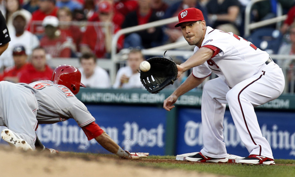 Photo - Washington Nationals first baseman Greg Dobbs (33) waits for the throw as Cincinnati Reds' Billy Hamilton (6) jumps back safely to first base during the third inning of a baseball game at Nationals Park Monday, May 19, 2014, in Washington. (AP Photo/Alex Brandon)