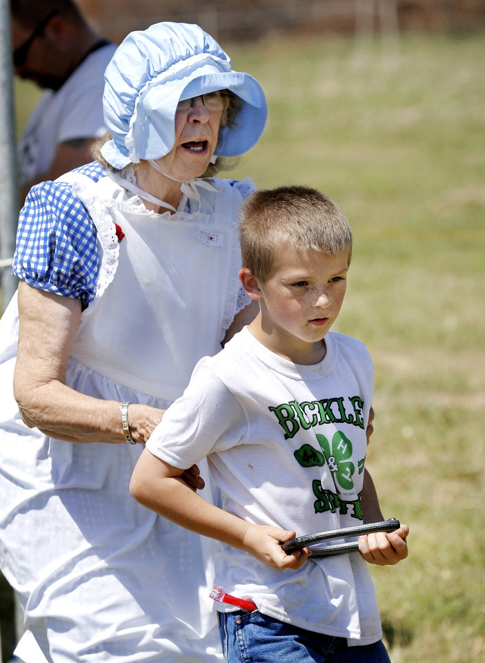 "Photo - Volunteer Joyce Stockton stands behind Josh Ayers, 7, from Antlers, Okla., and helps him get into position as he prepares to play horse shoes. Stockton is with women from Grady County Rural Neighbors, Oklahoma Home and Community Education Group, in Chickasha, who hosted a tent where children could play ""non-electronic"" games typical of ones played by young people in the early 1900s.  Children were able to compete in sack races, toss horseshoes, play jacks, jump rope,  and engage in other assorted fun physical activities.  Oklahoma Cooperative Extension Service celebrated their 100th anniversary with a Whistle Stop and Festival on Saturday, April, 12, 2014 at the Rock 'N Rail yard near Highway 66 in Wellston, Oklahoma.  ""In the early 1900s, trains were the modern way to travel and early Extension agents were allowed to 'ride the rails', going from town to town presenting demonstrations  and showing people how they might improve the quality of their lives by making use of the latest science-proven advances, practices and products,"" said James Trapp. OCES associate director. A train coming into town was sometimes referred to  as a ""county fair on wheels."" As part of its centennial celebration, Extension conducted an historic reenactment  of the type of whistle stop tours that would have occurred   in 1914. Visitors  at the festival were given the opportunity to visit a variety of tents and booths offering demonstrations and hands-on activities representative of Extension programs. Photo by Jim Beckel, The Oklahoman"