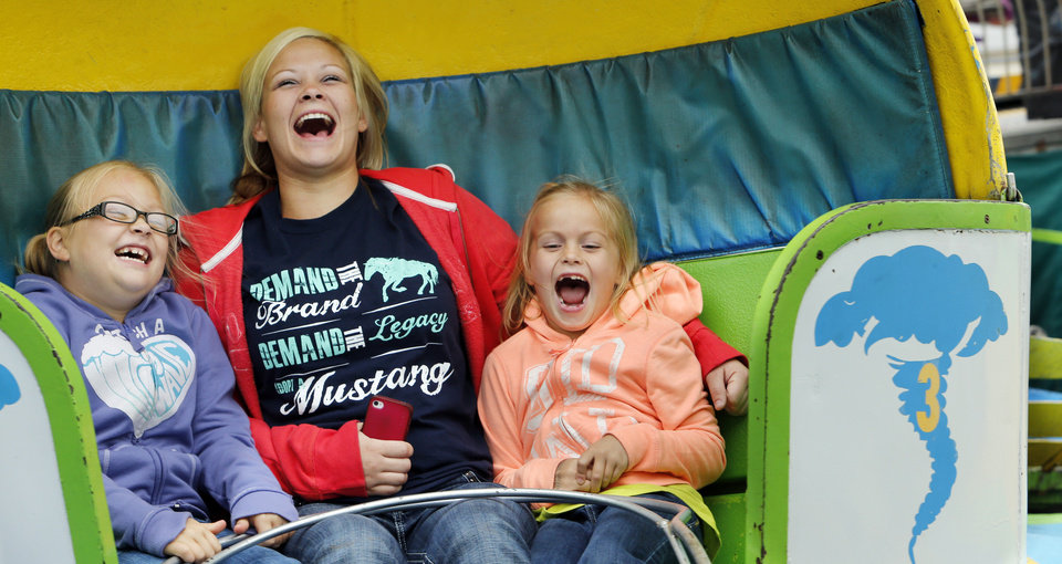 Fairgoers Faith Simpson, 8 left, and sister Faith, 6 right, ride the Tilt a Whirl with Nina Pearman, center, at the 106th Oklahoma State Fair at State Fair Park on Saturday, Sept. 15, 2012, in Oklahoma City, Okla.  Photo by Steve Sisney, The Oklahoman