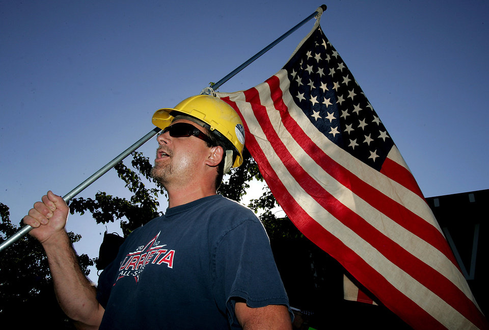 Photo - Paul Hathaway, of Murrieta, Calif., holds a U.S. flag as he shouts outside Murrieta Mesa High School in Murrieta, Calif., where city, Riverside County and federal officials spoke about a  plan to process immigrants detained in Texas at the Murrieta U.S. Border Patrol facility, Wednesday, July 2, 2014. (AP Photo/The Press-Enterprise, Terry Pierson)