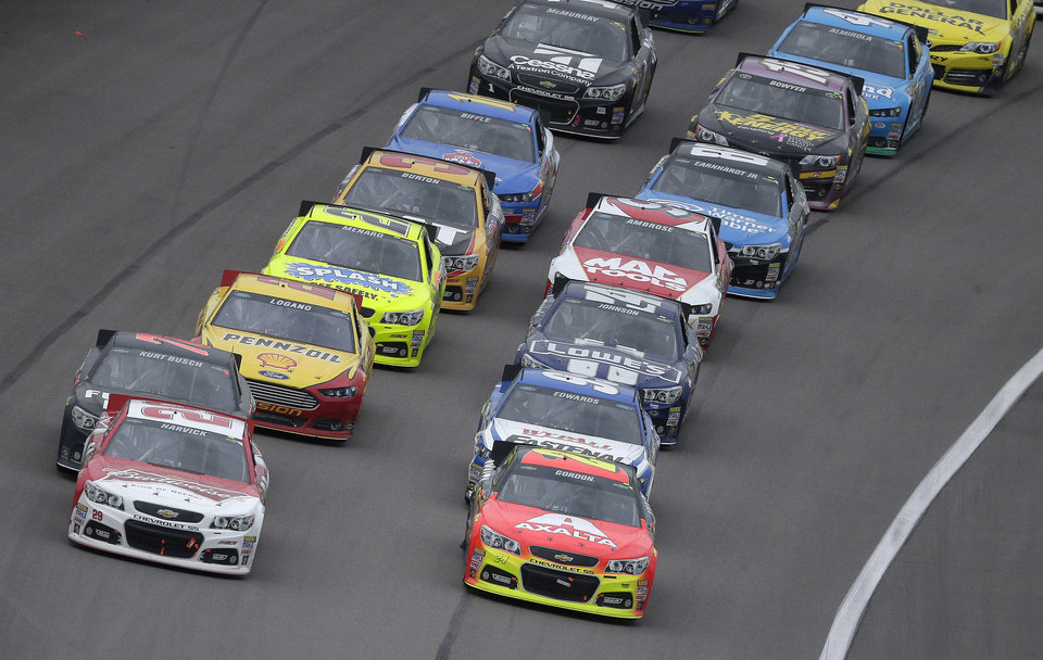 Photo - Driver Kevin Harvick, front left, leads the pack coming out of a caution with 20 laps to go in the NASCAR Sprint Cup series auto race at Kansas Speedway in Kansas City, Kan., Sunday, Oct. 6, 2013. Harvick went on to win the race. (AP Photo/Charlie Riedel)