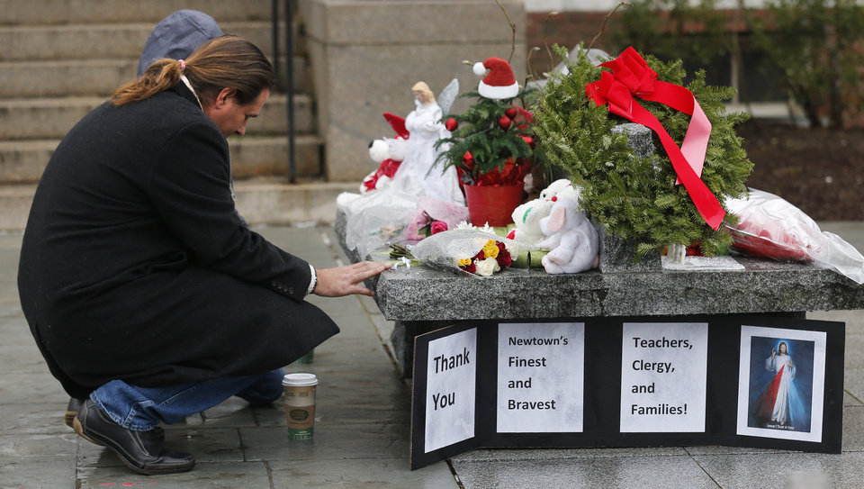 Photo - A couple pause at a memorial outside town hall in Newtown, Conn., Monday, Dec. 17, 2012. A gunman opened fire at Sandy Hook Elementary School in the town, killing 26 people, including 20 children before killing himself on Friday. (AP Photo/Charles Krupa) ORG XMIT: CTCK110