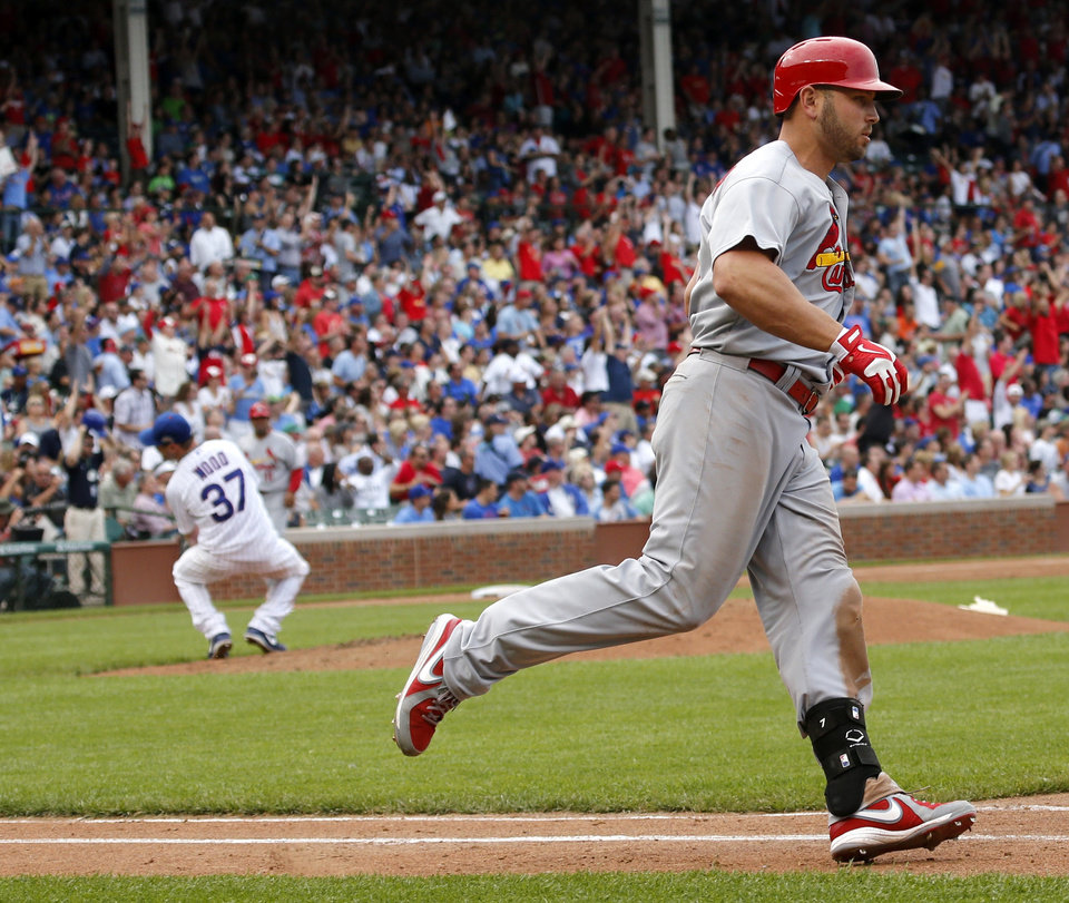 Photo - St. Louis Cardinals' Matt Holliday rounds the bases after hitting a home run off Chicago Cubs starting pitcher Travis Wood, background left, during the fifth inning of a baseball game Friday, July 25, 2014, in Chicago. (AP Photo/Charles Rex Arbogast)