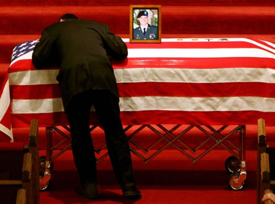 Photo -  CPL. GARY L. MOORE / IRAQ WAR / OKLAHOMAN / DEATHS / ARMY MILITARY POLICEMAN / FUNERAL: A relative of Gary Moore hugs his casket as services for Gary Moore begin at Southwest Baptist Church in Oklahoma City on Tuesday, March 24, 2009. Moore was killed in Iraq last week. PHOTO BY JOHN CLANTON, THE OKLAHOMAN ORG XMIT: KOD
