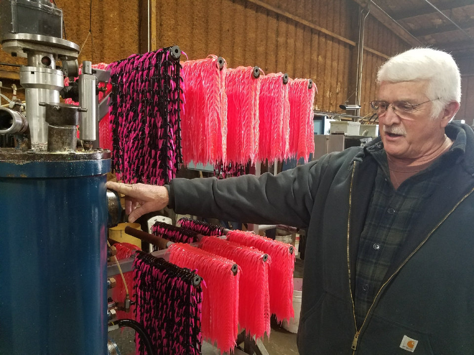Photo -  George Toalson, product designer and plant manager for Bobby Garland Crappie Baits, explains the soft plastic mold injection machines used to make the crappie baits. [PHOTO BY ED GODFREY, THE OKLAHOMAN]
