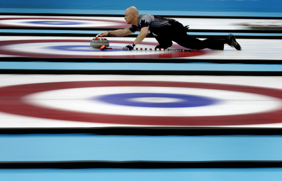 Photo - Canada's Ryan Fry delivers the rock during the men's curling gold medal game against Britain at the 2014 Winter Olympics Friday, Feb. 21, 2014, in Sochi, Russia. (AP Photo/Wong Maye-E)