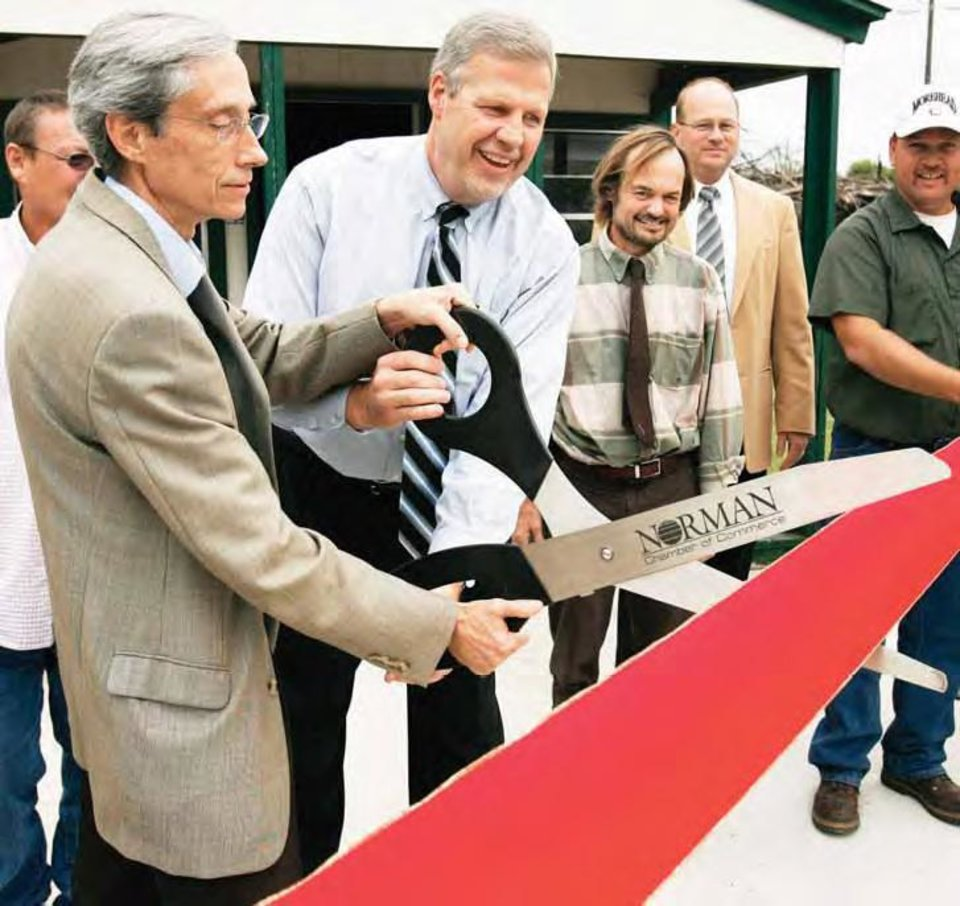 City Councilman Doug Cubberley, left, helps City Manager Steve Lewis cut a ribbon at the grand opening of Norman�s new compost center. OKLAHOMAN ARCHIVE PHOTO