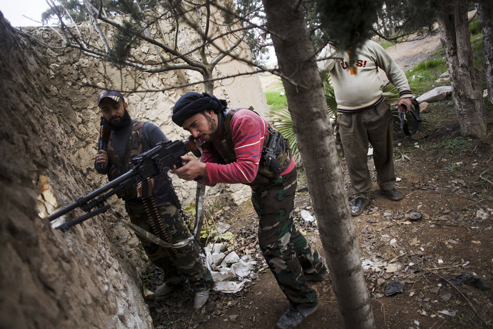 A Free Syrian Army fighter fires at Syrian Army positions during an attack on a military academy in Tal Sheer village, north of Aleppo province, Syria, Thursday, Dec. 13, 2012 (AP Photo/Manu Brabo) ORG XMIT: CAI114