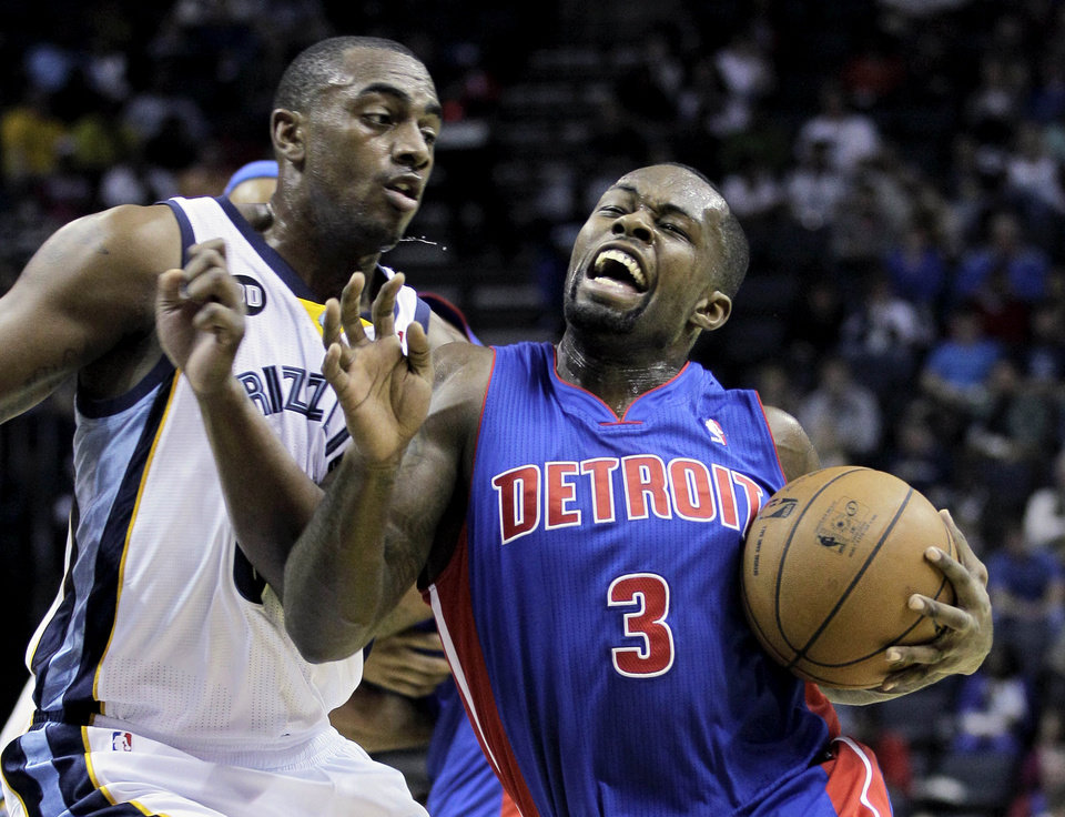Photo - Detroit Pistons' Rodney Stuckey (3) goes under Memphis Grizzlies' Darrell Arthur, left, during the first half of an NBA basketball game in Memphis, Tenn., Friday, Nov. 30, 2012. (AP Photo/Danny Johnston)