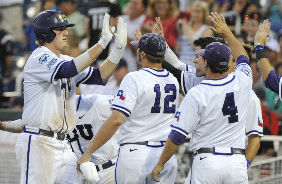 Photo - TCU's Kevin Cron, left, celebrates at the dugout with teammates Riley Ferrell (12) and Connor Castellano (4) after he hit a solo home run against Mississippi in the fifth inning of an NCAA baseball College World Series elimination game in Omaha, Neb., Thursday, June 19, 2014. (AP Photo/Eric Francis)
