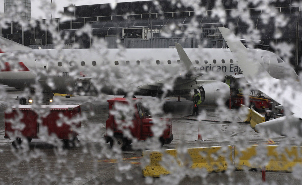Photo - Window on an American Eagle plane is covered with snow before it is de-iced at O'Hare International Airport Sunday, Dec. 22, 2013, in Chicago. As Americans and Canadians ushered in the first official day of winter, the weather provided a variety of surprises. Snow and ice hit Michigan, Canada, New England and upstate New York. Some other eastern regions had temperatures in the 60s and 70s. (AP Photo/Kiichiro Sato)