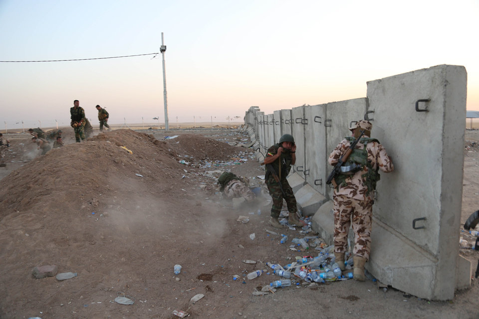 Photo - Kurdish Peshmerga fighters take cover during airstrikes targeting Islamic State militants near the Khazer checkpoint outside of the city of Irbil in northern Iraq, Friday, Aug. 8, 2014. Iraqi Air Force has been carrying out strikes against the militants, and for the first time on Friday, U.S. war planes have directly targeted the extremist Islamic State group, which controls large areas of Syria and Iraq. (AP Photo/ Khalid Mohammed)