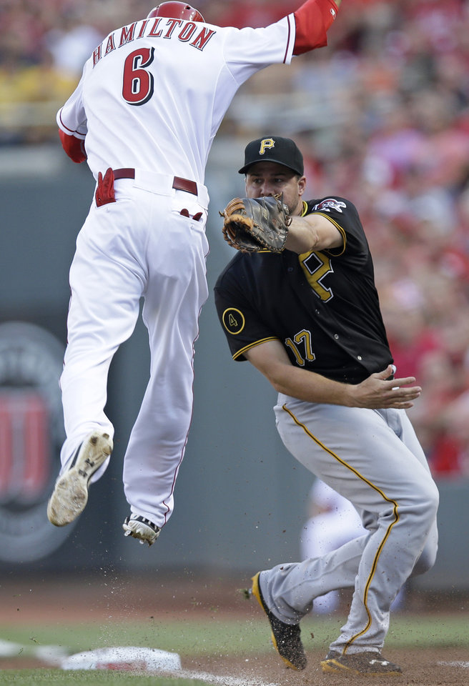 Photo - Cincinnati Reds' Billy Hamilton (6) jumps in the air to avoid a tag by Pittsburgh Pirates first baseman Gaby Sanchez (17) in the first inning of a baseball game, Friday, July 11, 2014, in Cincinnati. Hamilton was safe at first. (AP Photo/Al Behrman)