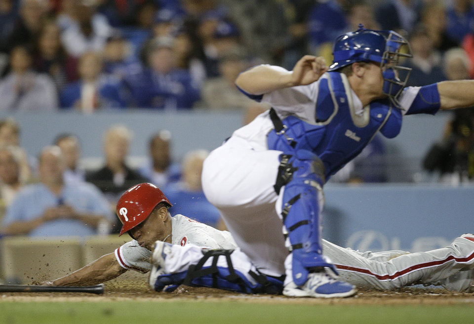 Photo - Philadelphia Phillies' Ben Revere, left, scores on a sacrifice hit by Ryan Howard as Los Angeles Dodgers catcher Tim Federowicz fields the throw during the fifth inning of a baseball game on Tuesday, April 22, 2014, in Los Angeles. (AP Photo/Jae C. Hong)