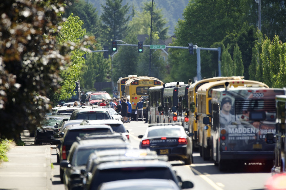 Photo - Students are led to waiting buses by police after a shooting at Reynolds High School in Troutdale, Ore., Tuesday, June, 10, 2014. A gunman killed a student at the high school east of Portland Tuesday and the shooter is also dead, police said. (AP Photo/Troy Wayrynen)