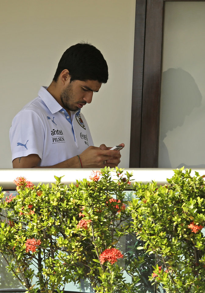 Photo - Uruguay's Luis Suarez uses his cell phone at a hotel in Natal, Brazil, Wednesday, June 25, 2014. Suarez bit Italian player Giorgio Chiellini during Uruguay's game with Italy on Tuesday, which could lead to Suarez being kicked out of the World Cup. (AP Photo/Hassan Ammar)