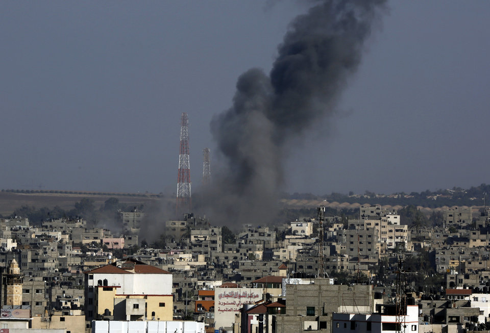 Photo - Smoke rises after an Israeli strike hit Gaza City in the northern Gaza Strip, Tuesday, Aug. 19, 2014. The Israeli military said it carried out a series of airstrikes Tuesday across the Gaza Strip in response to renewed rocket fire, a burst of violence that broke a temporary cease-fire and endangered negotiations in Egypt over ending the month long war between Israel and Hamas. The fighting occurred some eight hours before a temporary truce was set to expire. (AP Photo/Adel Hana))
