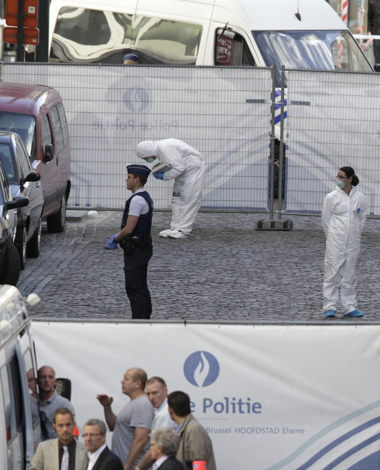 Photo - Forensic experts examine the site of a shooting at the Jewish museum in Brussels, Saturday, May 24, 2014. Belgian officials say that at least three people have been killed in gunfire at the Jewish Museum in Brussels. Belgian Foreign Minister Didier Reynders, in a post on Twitter, said he was