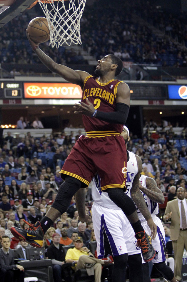 Photo - Cleveland Cavaliers guard Kyrie Irving, left, goes to the basket against Sacramento Kings center DeMarcus Cousins during the first quarter of an NBA basketball game in Sacramento, Calif.,  Sunday, Jan. 12, 2014.  (AP Photo/Rich Pedroncelli)