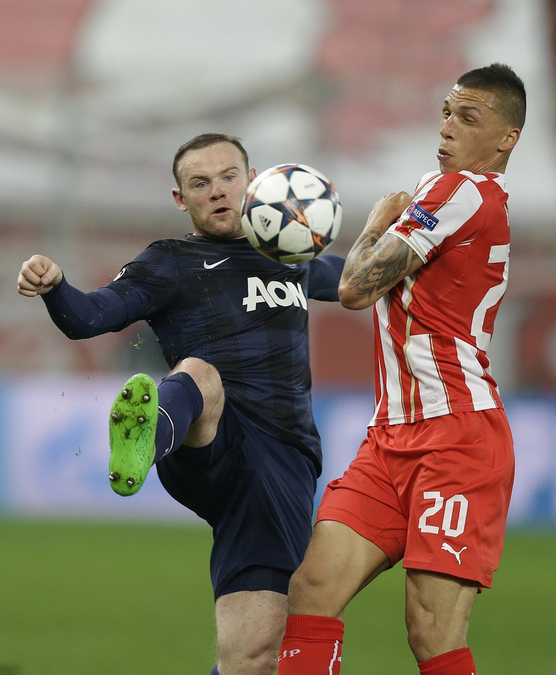 Photo - Olympiakos' Jose Holebas, right, fights for the ball with Manchester United's Wayne Rooney during their Champions League, round of 16, first leg soccer match at Georgios Karaiskakis stadium, in Piraeus port, near Athens, on Tuesday, Feb. 25, 2014. (AP Photo/Thanassis Stavrakis)