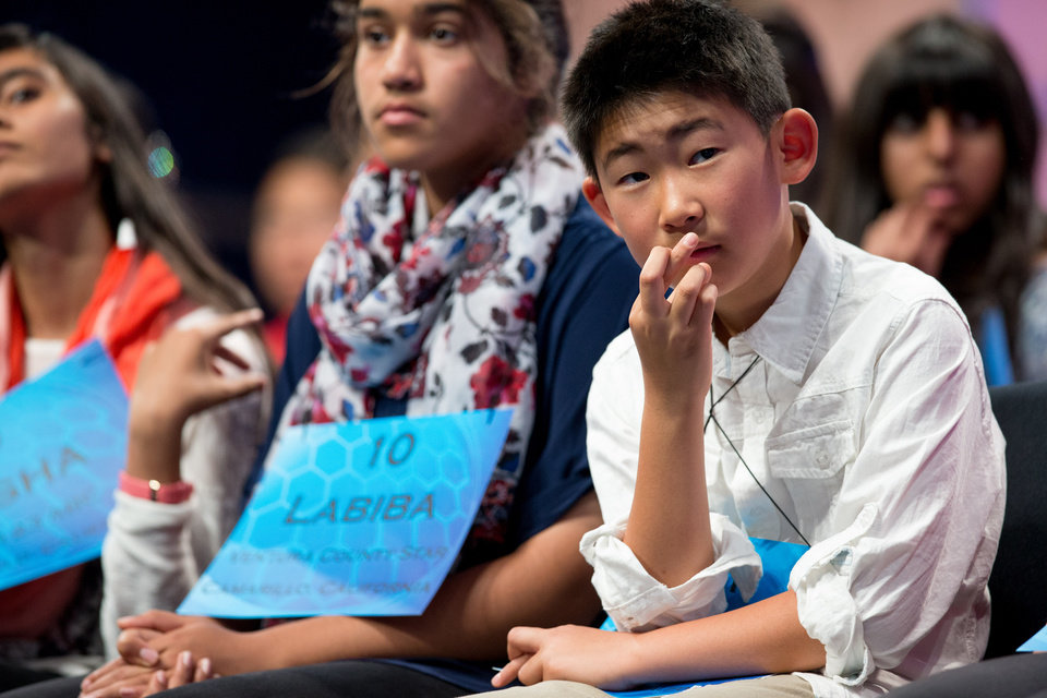 Photo - Nicholas Lee, 11, of Diamond Bar, Calif., right, crosses his fingers as he and others listen to a speller during the 2015 Scripps National Spelling Bee, Wednesday, May 27, 2015,  in Oxon Hill, Md. (AP Photo/Andrew Harnik)